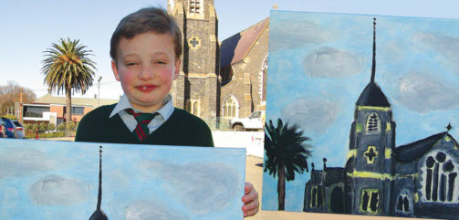 Liam, 12, of Sacred Heart Catholic Primary School, holds his painting, The Church, outside the Church of the Apostles in Launceston.